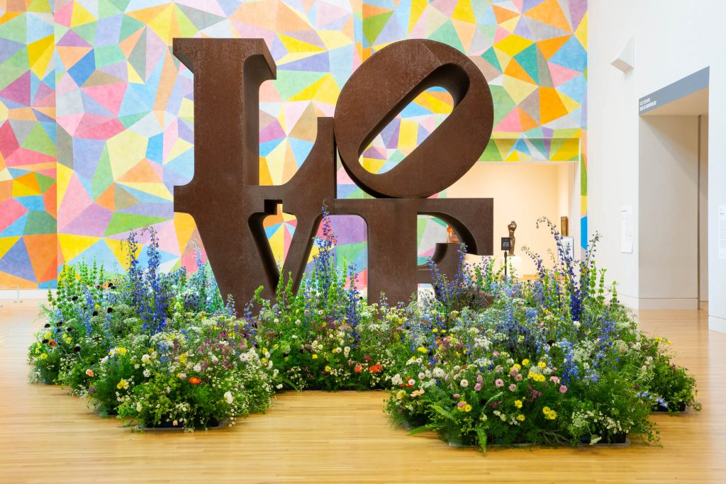 Image of Installation view of Art in Bloom. Robert Indiana (American, 1928–2018), LOVE, 1970, Cor-ten steel, 144 × 144 × 72 in. Indianapolis Museum of Art at Newfields, Gift of the Friends of the Indianapolis Museum of Art in memory of Henry F. DeBoest. Restoration was made possible by Patricia J. and James E. LaCrosse, 75.174 © Morgan Art Foundation / Artists Rights Society (ARS), New York.