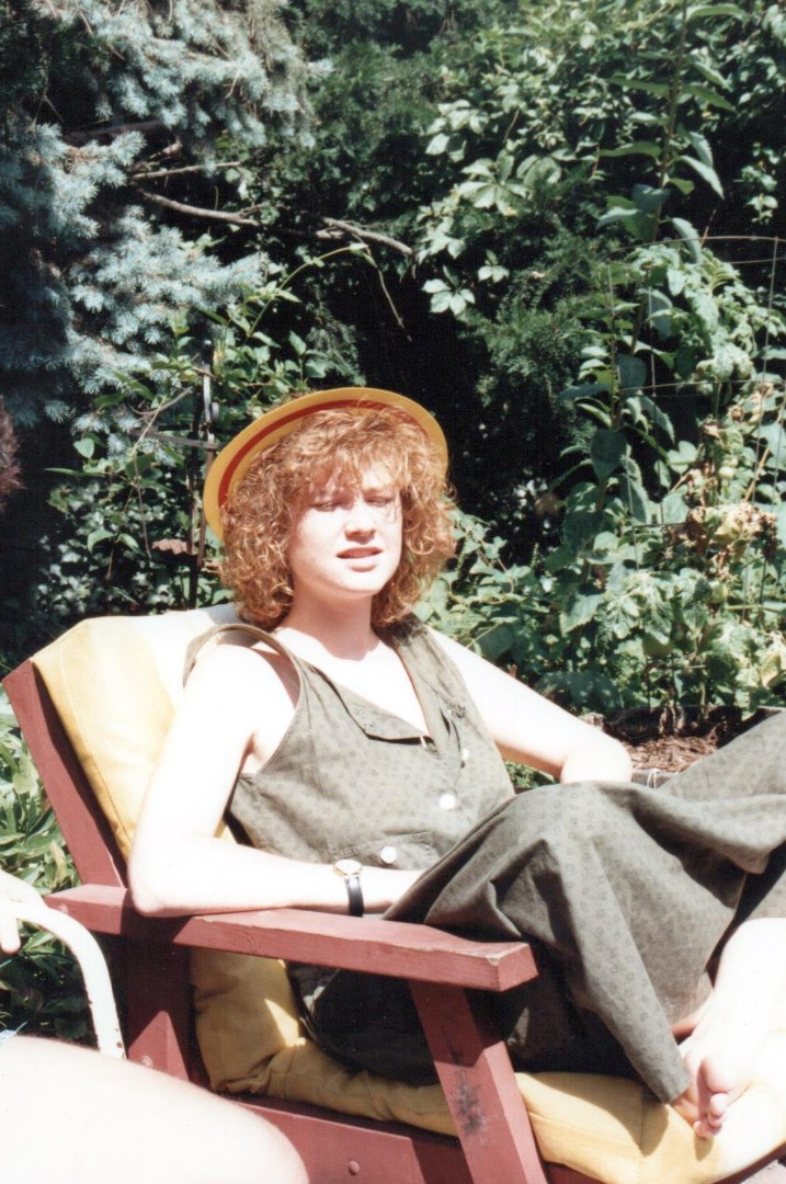 A young women sits cross-legged in a garden patio on a sunny day.